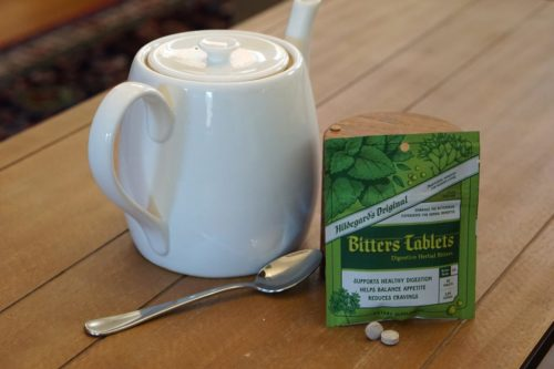 A steeping pot, spoon and package of Hildegard's Original Bitters Tablets
